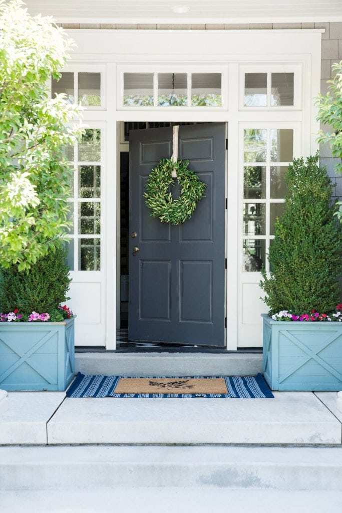 A traditional front porch with blue wood planters filled with boxwood topiaries and impatiens.