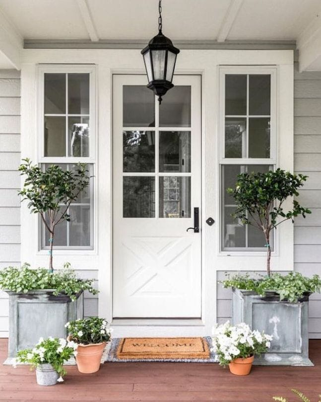 A beautiful gray home with white front door. The galvanized planters are filled with topiaries and the terra cotta pots are filled with white petunias.