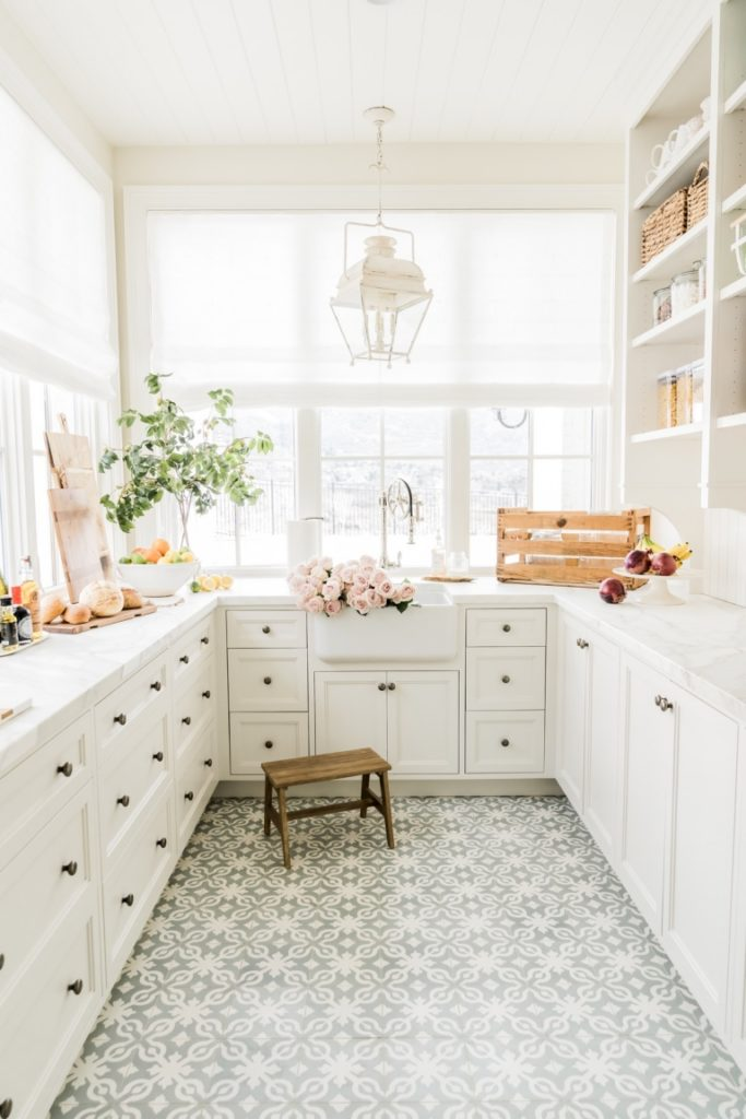 A gorgeous pantry with white cabinets, windows, gray and white patterned cement tile floors, a white lantern and French style accents.