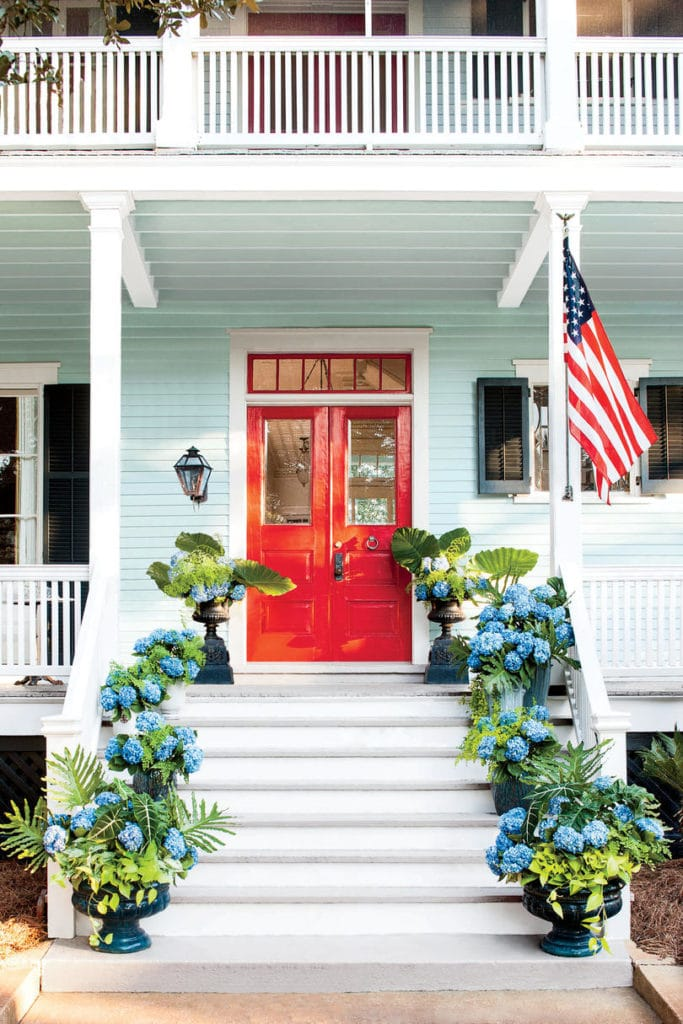 An aqua home with a bright red front door and large porch. The steps leading to the home are filled with potted blue hydrangeas.