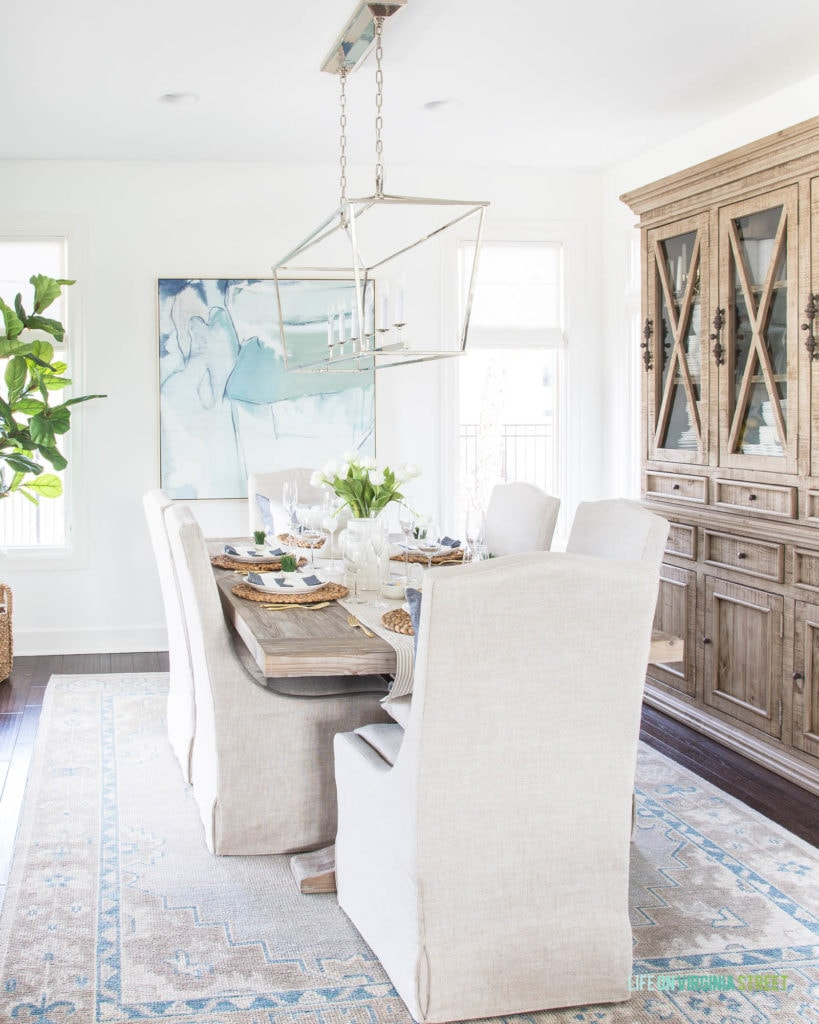 A spring dining room with an Easter tablescape. I love the neutrals mixed with blues and greens. The linen chairs and wood dining table pair perfectly with the more modern chandelier!