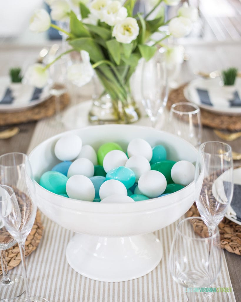 A white ceramic footed bowl filled with faux Easter eggs! Such a fun decorating idea for spring or Easter!