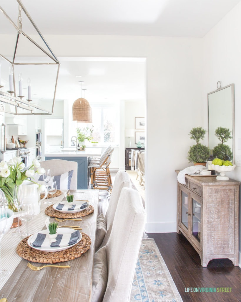 A coastal inspired Easter tablescape with linen chairs, reclaimed wood dining table, navy blue and white striped napkins and pillows, water hyacinth chargers and more! Such pretty spring decorating ideas!