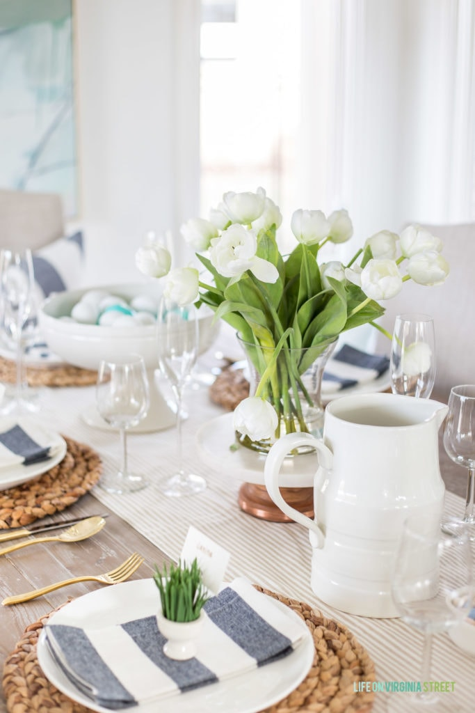 An Easter tablescape with white ceramic serving pieces, a faux white tulip flower arrangement, sisal chargers and striped napkins.