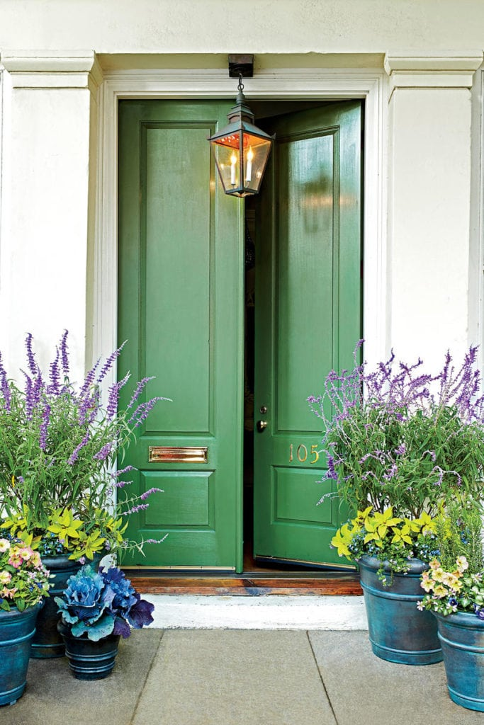 A beautiful bold green front door that is slightly ajar paired with planters filled with purple flowers and green foliage.