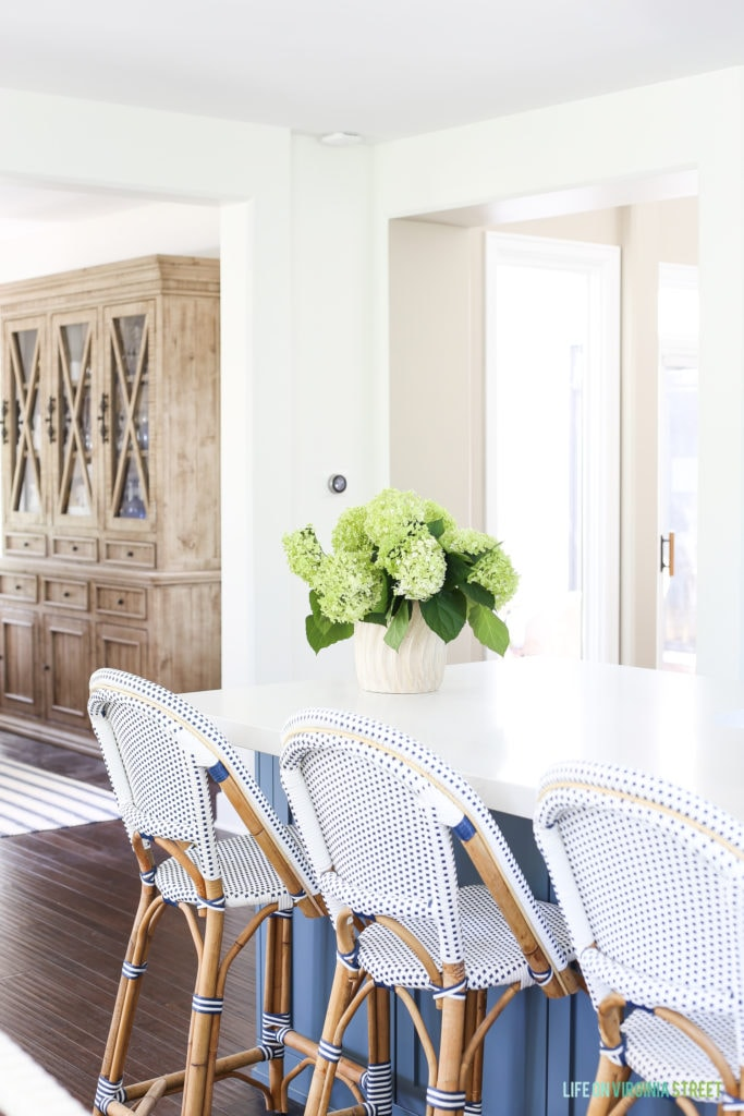 A kitchen island with hydrangeas on the top and chairs around it.