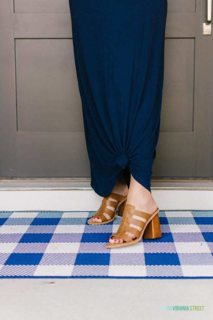 A dark blue dress and neutral sandals on a woman.