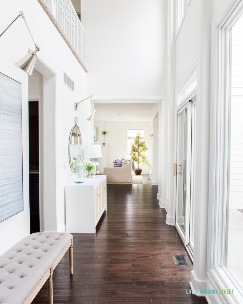 A bright entryway hallway with floor to ceiling windows, a gray tufted bench, white cane cabinet, swing arm sconces, a round mirror and tulips for spring!