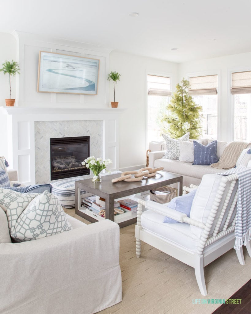 A spring living room with blue and white stripes and faux green topiaries.