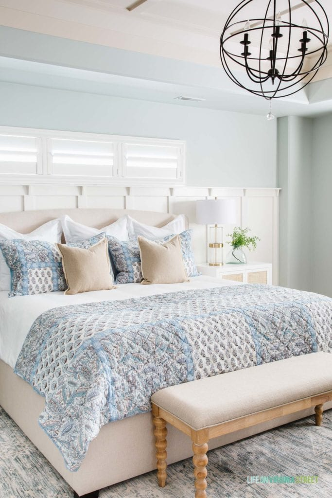 A blue and white bedroom decorated for spring with a spindle leg bench, paisley bedding, orb chandelier, linen pillows, and gold lamp.