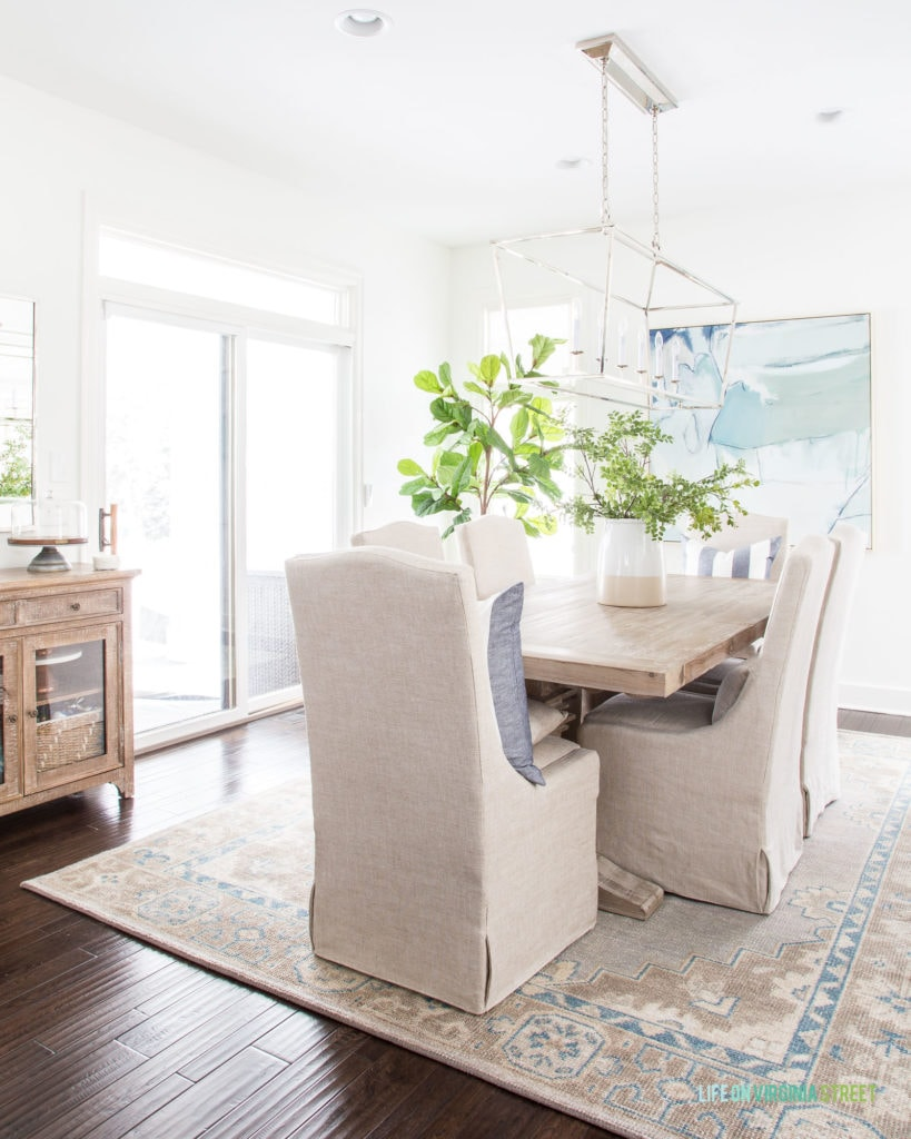The vintage inspired rug with the wooden table with fabric chairs in the living room.