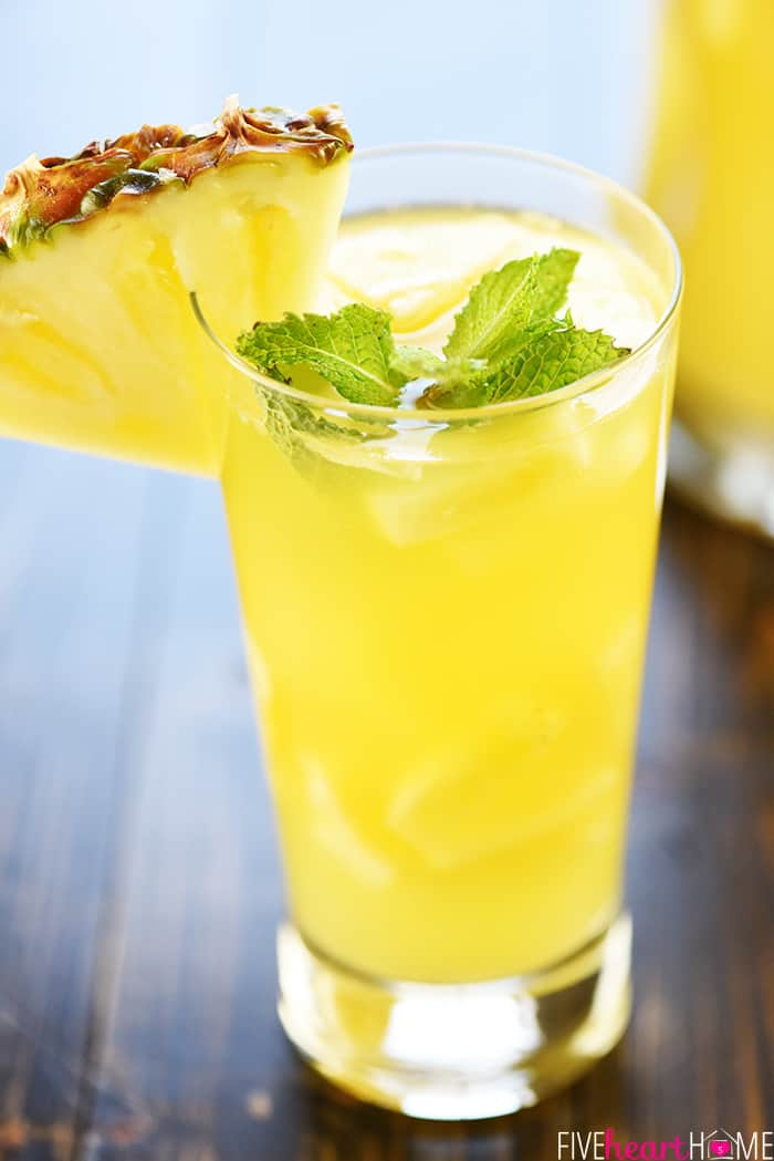 Sparkling Pineapple Sangria with a slice of pineapple on the rim of the cup.