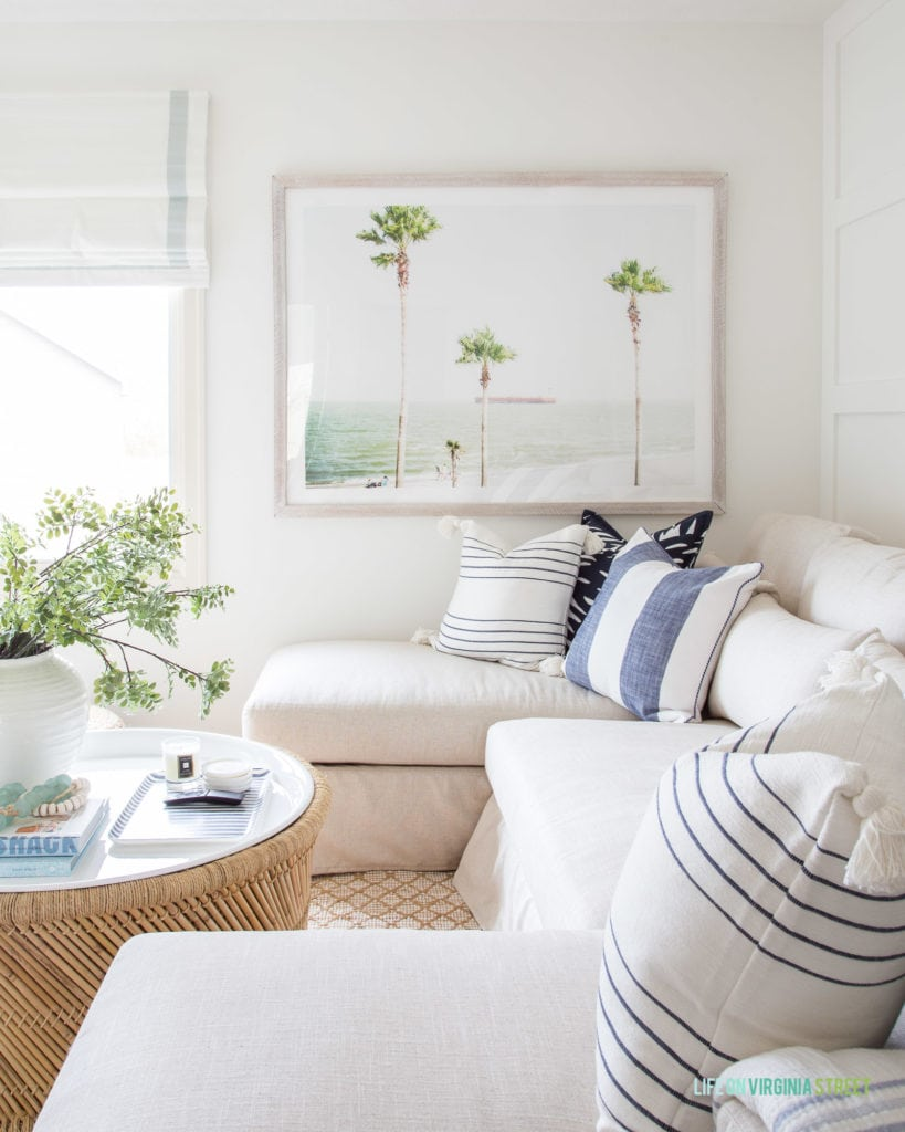 Palm tree art in a coastal den design. I love all of the blue, white and neutral accents in this TV room!