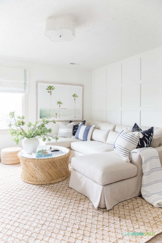 The white Pottery Barn sectional couch in a living room with a round coffee table.