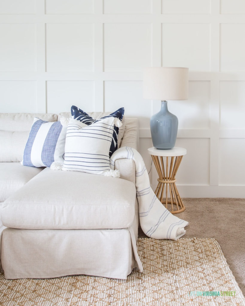 A white board and batten grid wall with a linen sectional, blue gray lamp, bamboo and white resin side table, and blue and white striped pillows.