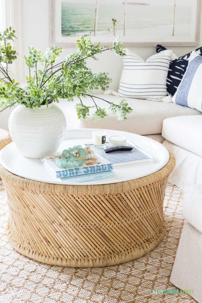 A coastal bamboo coffee table with white enamel tray top that is durable and great for indoor or outdoor use! Decorated with a vase of greenery, a blue and white linen tray for TV remotes, and various beach inspired books and glass beads.