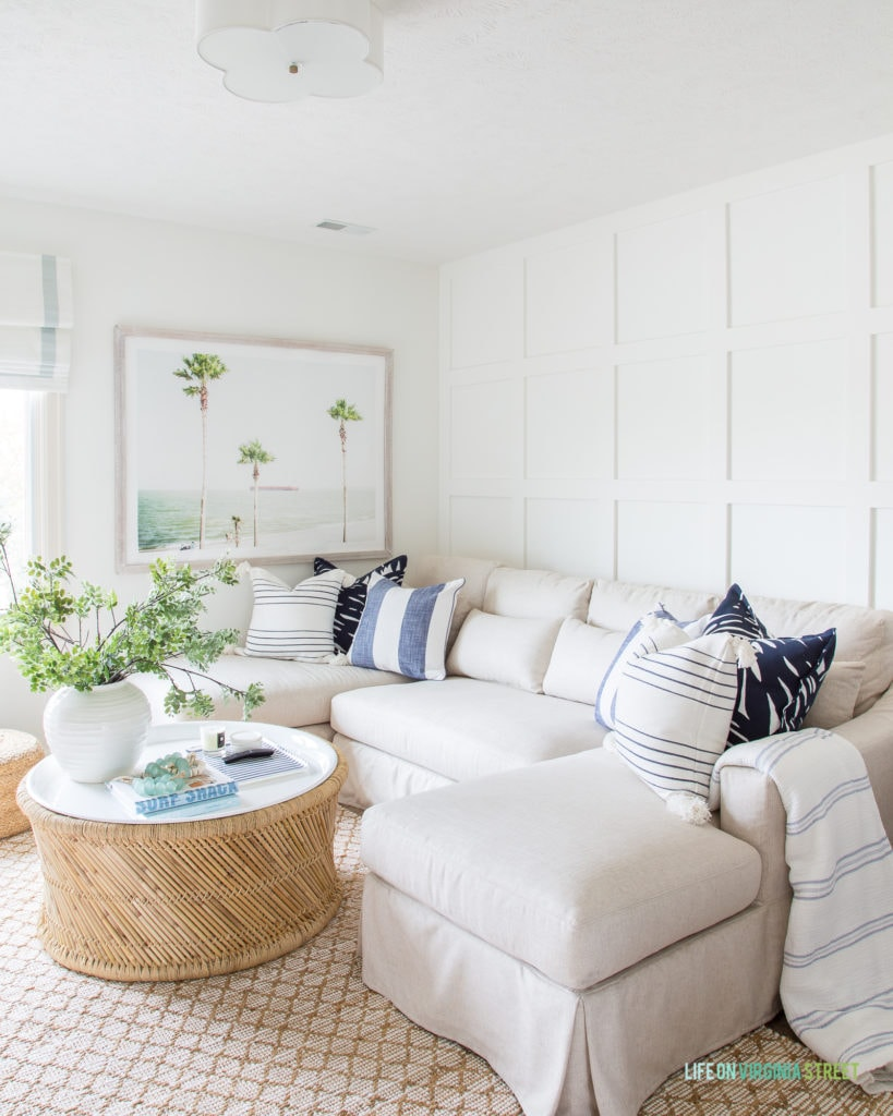 Den furniture ideas with a coastal flair. I love this beautiful linen sectional, bamboo and enamel coffee table, palm tree and ocean art, a scallop light fixture, and blue and white pillows. I also love the board and batten grid wall feature!