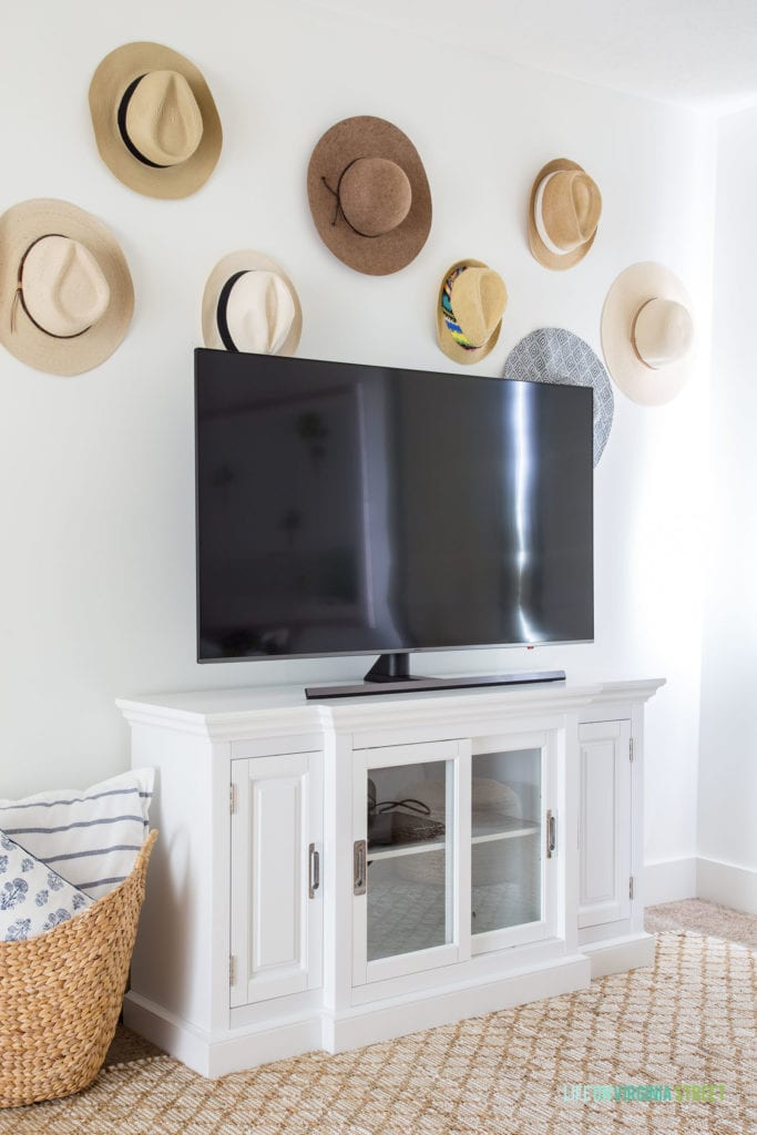 Cute idea for decorating around a TV. These beach hats are a fun way to add personality and memories to the wall!