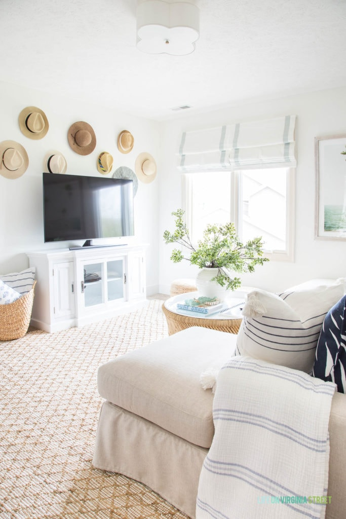 Den idea for decorating around a TV. I love the use of hats from vacations hung on the walls as memories.