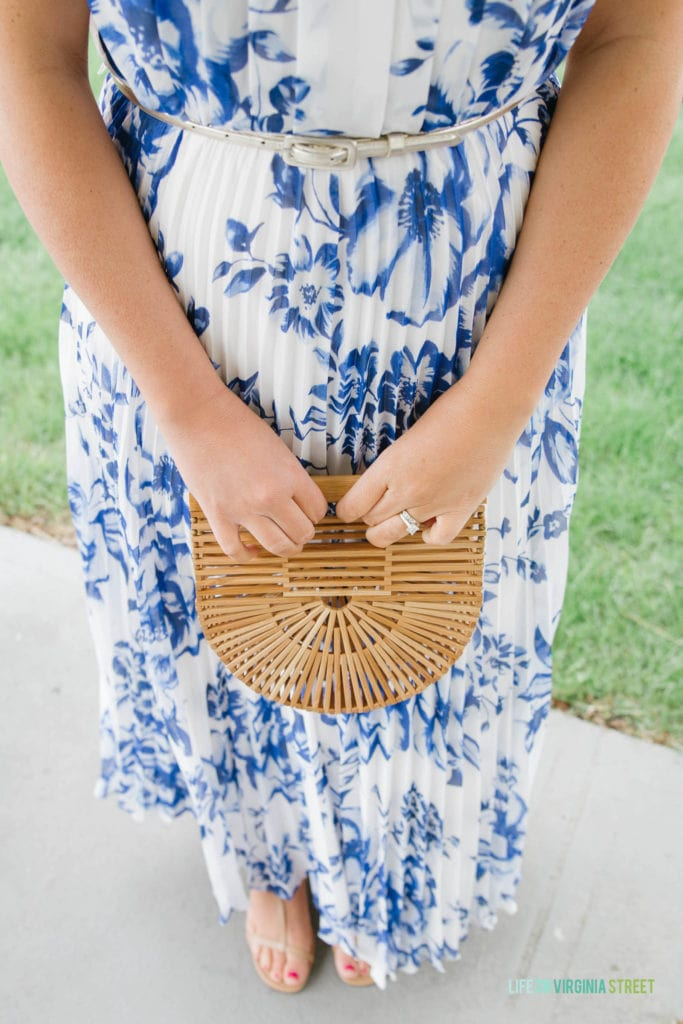 A woman holding a bamboo purse while standing up outside in the blue and white dress.
