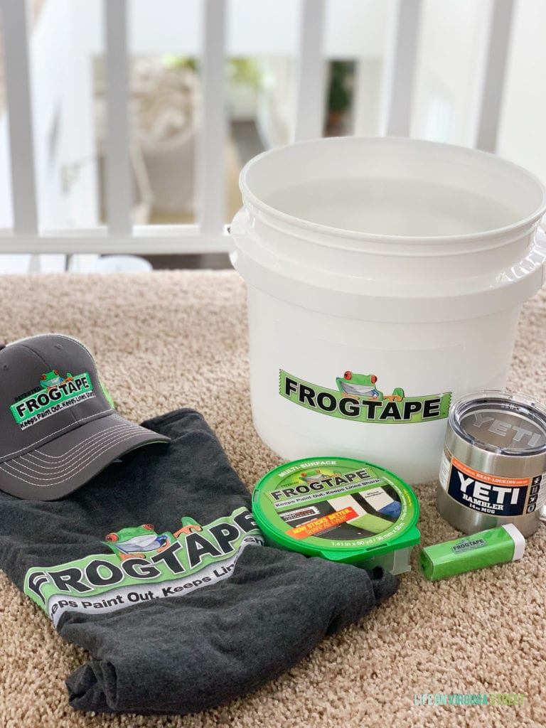 Frogtape hat, tape, shirt and bucket on the carpet.