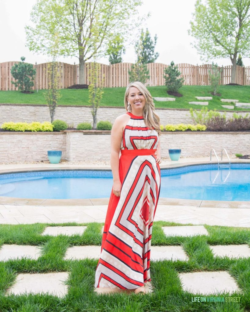 A red and white scarf printed long dress with the model standing in front of the pool.