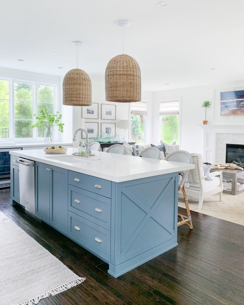 A coastal-inspired summer kitchen with white cabinets, a blue island, basket pendant lights and lots of greenery!