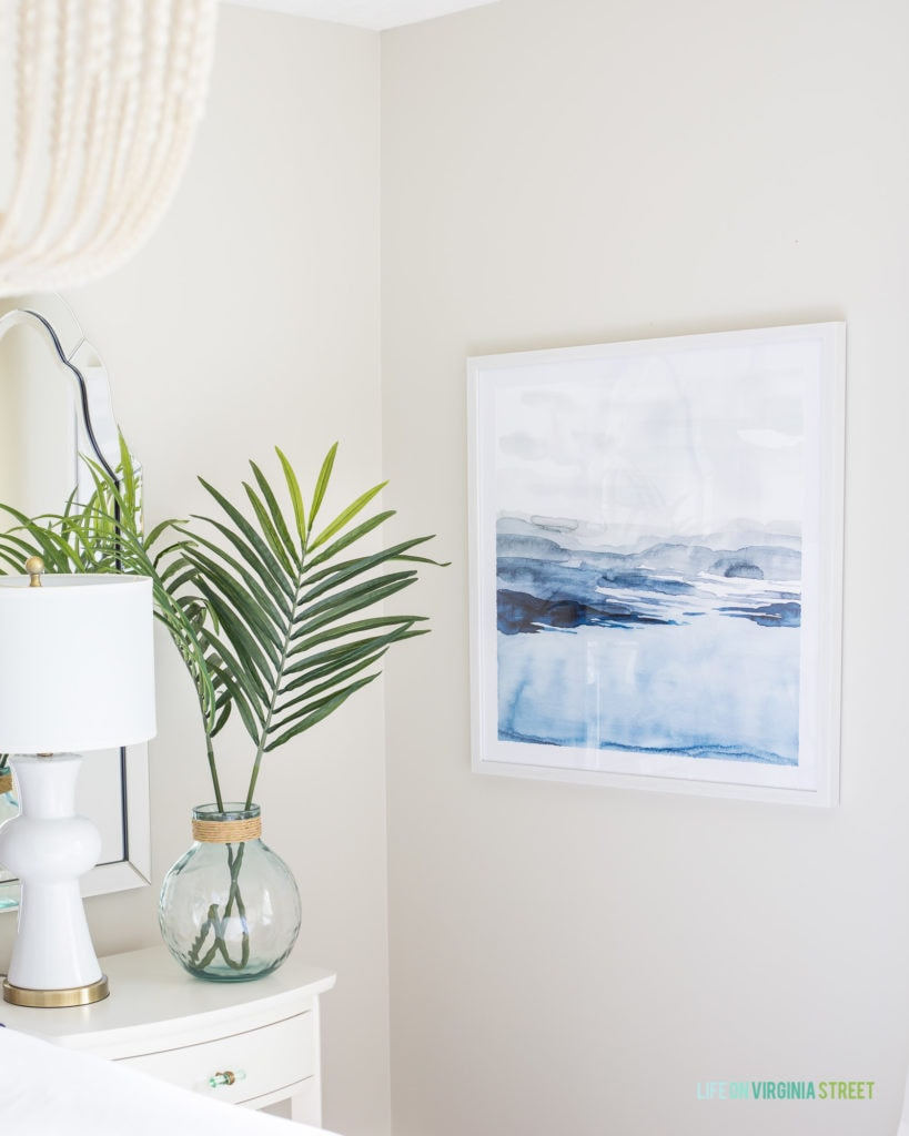 A clear vase on the side table in the bedroom with palm fronds in it and a beachy picture on the wall.