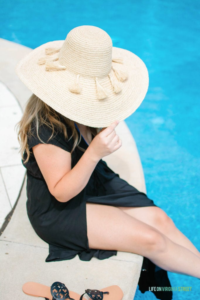The same person tipping the hat so you cannot see her face, while dipping her feet in the pool.