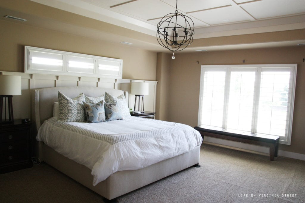 The bedroom with dark walls and a neutral bed. There is a light globe chandelier over the bed.