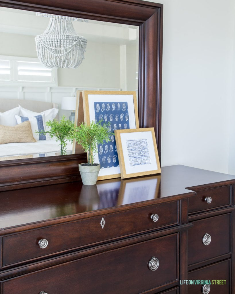 A dark wood dresser with framed pictures on it. A small topiary sits on top of the dresser and a chandelier is refelected in the mirror.
