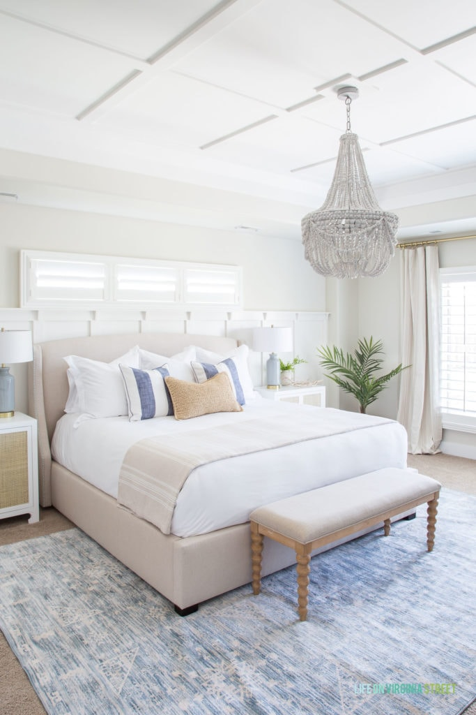A large bedroom with white bedding, a small light blue rug and a beaded chandelier.