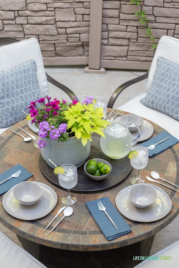 A beautiful outdoor dining tablescape featuring melamine dishes that look like ceramic, linen napkins, block print pillows, striped patio cushions, a gray ceramic flower pot, limes and more!