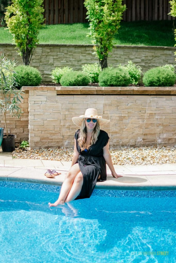 A smiling woman by the pool dipping her feet in.