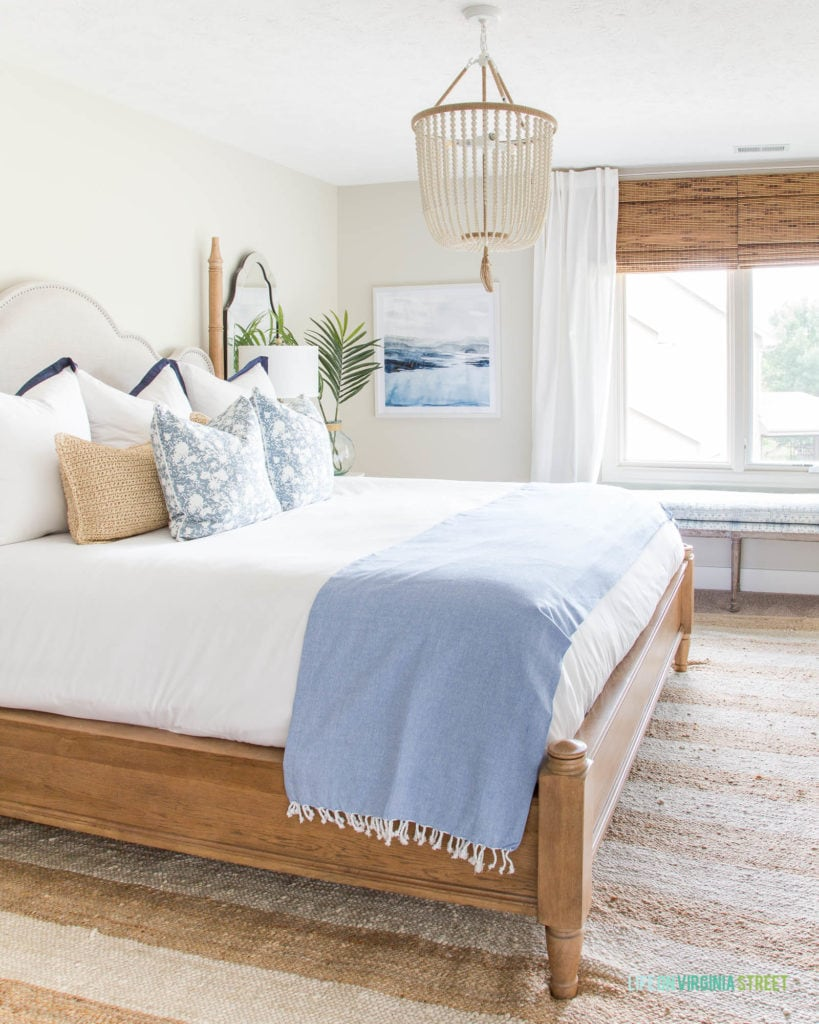 Summer guest bedroom updates with blue and white decor and natural wood tones. Love the white bead chandelier paired with the beachy watercolor artwork.