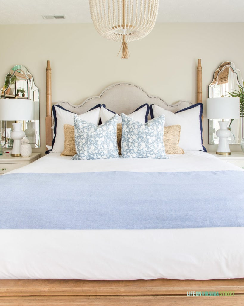 A fabric headboard, beaded chandelier, side tables, mirrors above the side tables in the light guest bedroom.