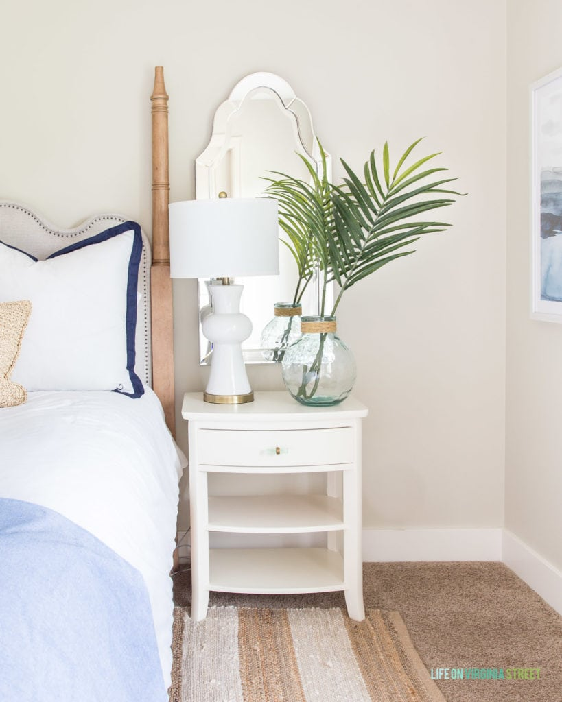 A white side table beside the bed in the guest bedroom.