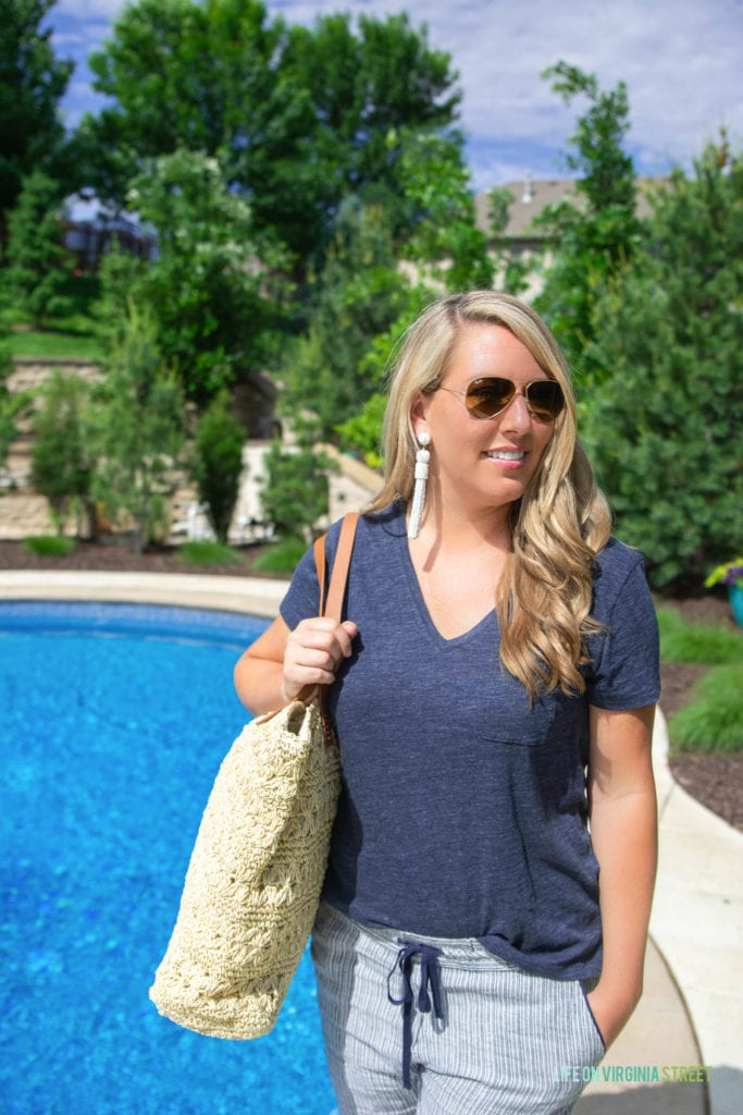 A woman standing beside the pool in aviator sunglasses, holding a beach bag.