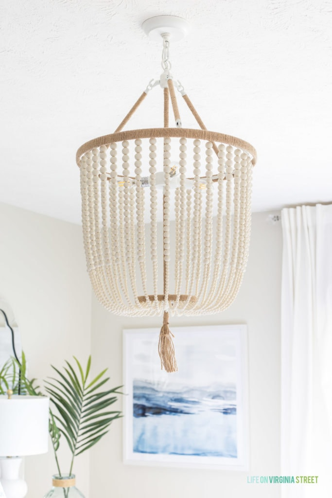 A white beaded chandelier hanging above the bed.