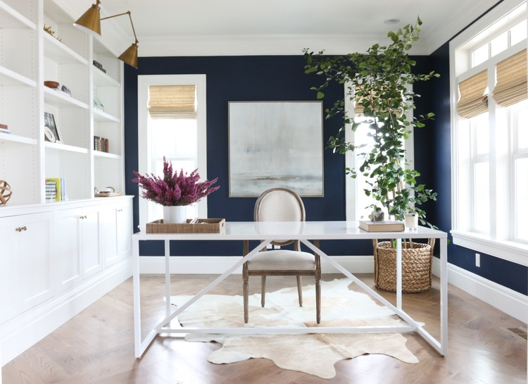 A home office with white built-in cabinets and walls painted Benjamin Moore Deep Royal, a pretty navy blue paint color idea.