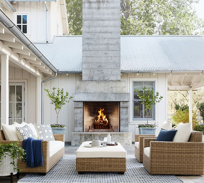 A beautiful outdoor courtyard idea with white house, white windows, woven wicker outdoor furniture, topiary trees, and blue and white accents.