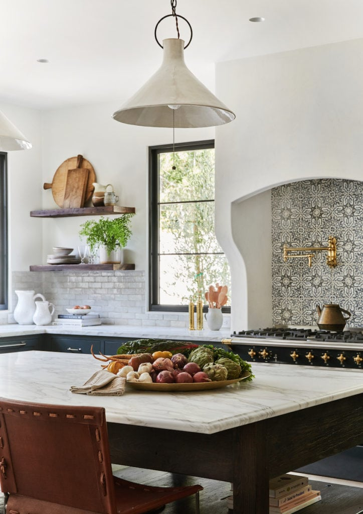 A gorgeous Spanish inspired kitchen with white stucco range, printed tile, black window panes, marble island top, leather chairs and warm accents. Designed by Amber Interiors and photographed by Tessa Neustadt