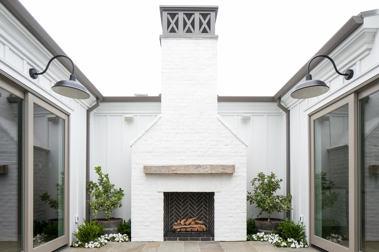 A white house with a brick outdoor fireplace, gray trim, large gray sliding doors, and barn lights in this area full of outdoor courtyard ideas.