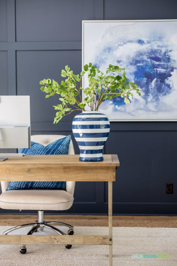 Faux ginkgo stems in a blue and white striped vase in a home office.