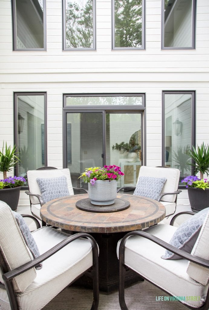 A brown fire pit table in a courtyard with a white house, black window trim, and coastal inspired accessories.