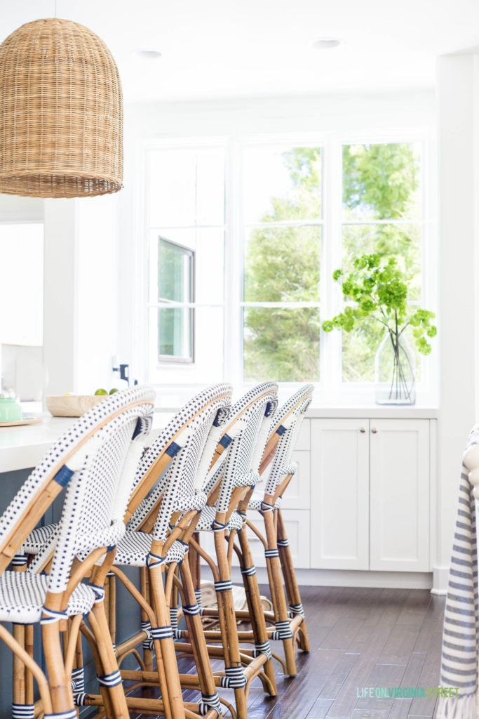 Blue and white bistro style bar stools in a coastal kitchen, with the basket light over the island in the kitchen.