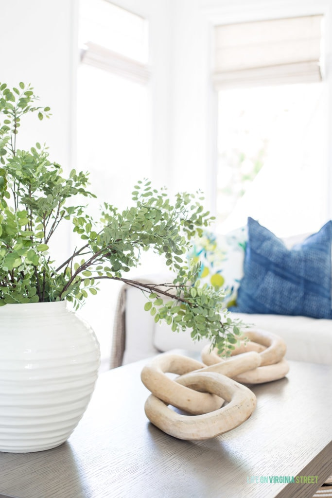 A white vase with a green plant on the coffee table beside a white large anchor chain.