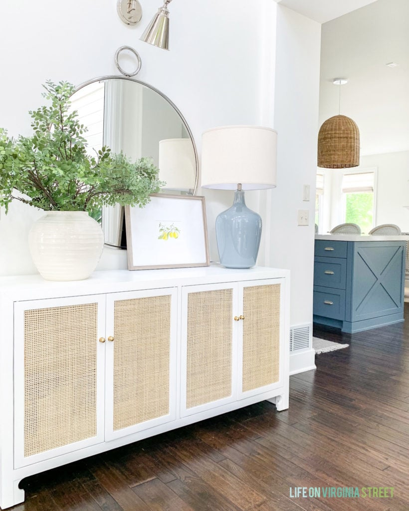 A white and cane console table decorated with faux greenery, lemon art, and a large ceramic lamp.