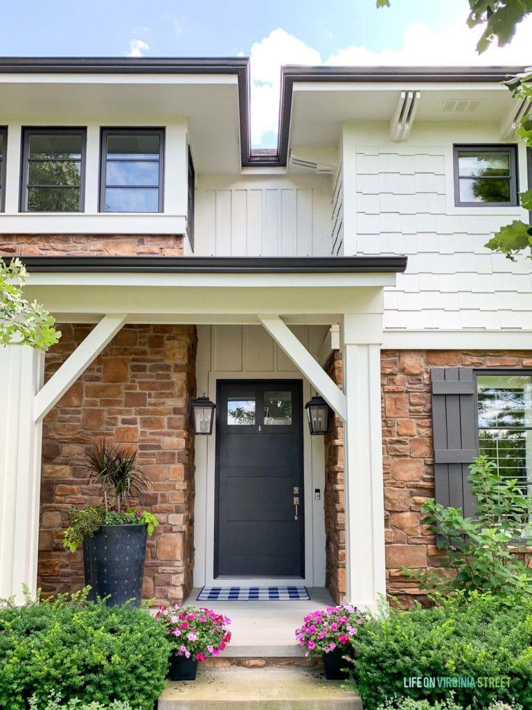 A beautiful white shingle exterior home with warm stone, black windows, lantern light fixture, a buffalo check rug, and colorful flowers.