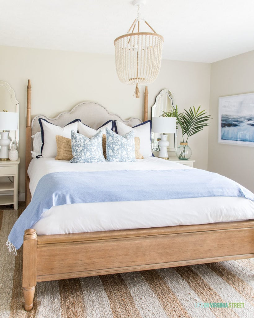 A large beaded chandelier over the neutral bed with two nightstands beside it.